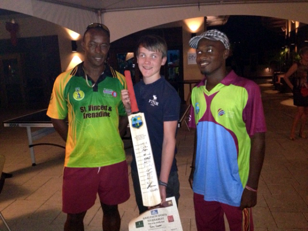 Deighton Butler (left) and Marvin Small (right) present John with his bat signed by the West Indies cricket team
